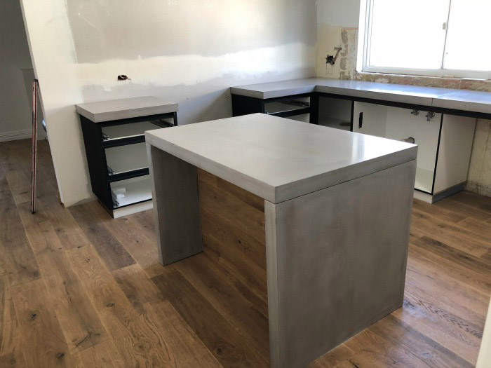 A kitchen refit with a concrete island and bench tops