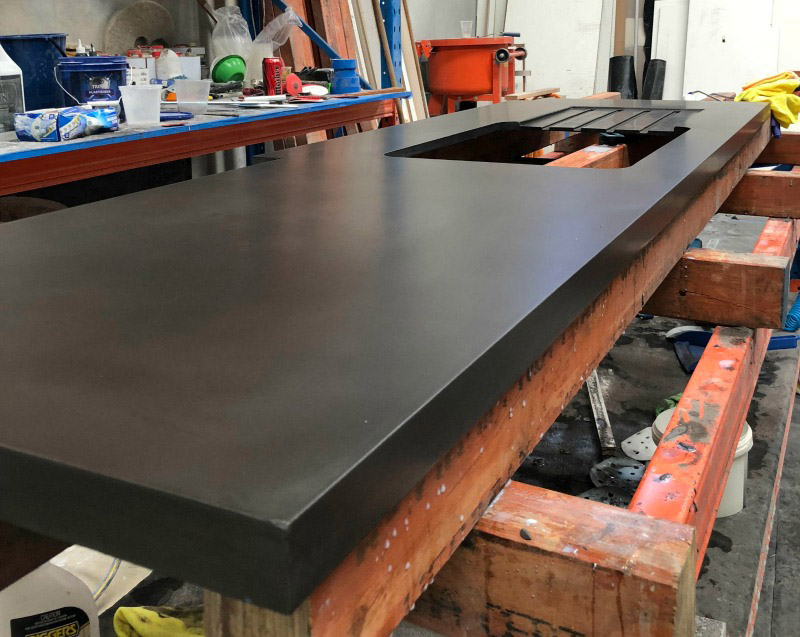 A dark coloured concrete bench top and sink cavity being manufactured in the concrete crib workshop