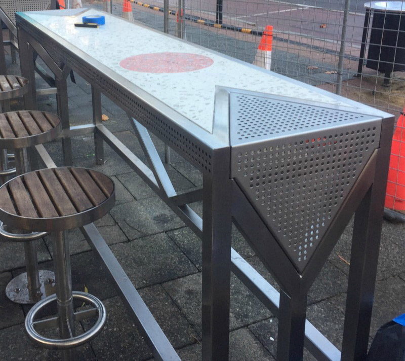 An outdoor table designed from stainless steel and concrete with matching stools