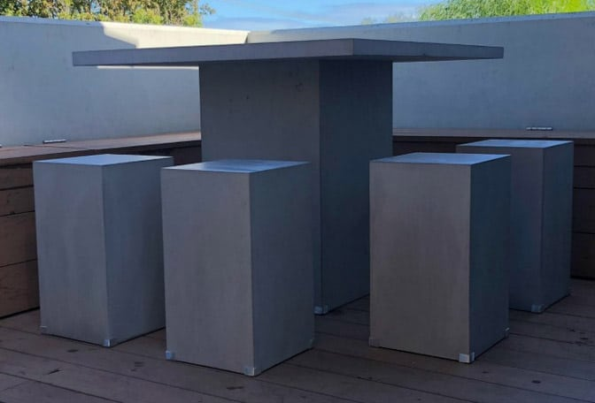 A classy concrete table and chairs for an outdoor setting